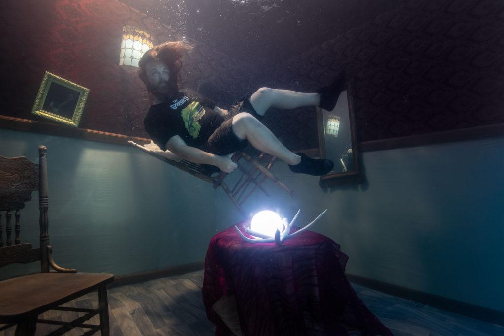 bearded man floating in an underwater room