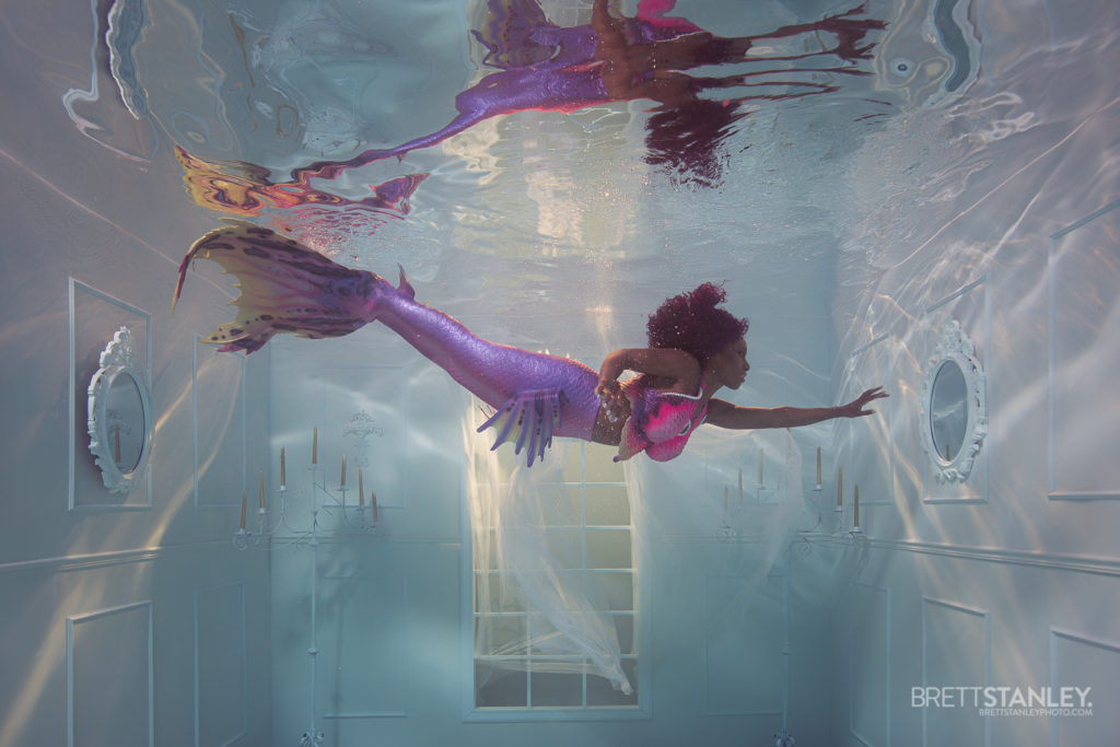 black mermaid in an underwater room for a photoshoot