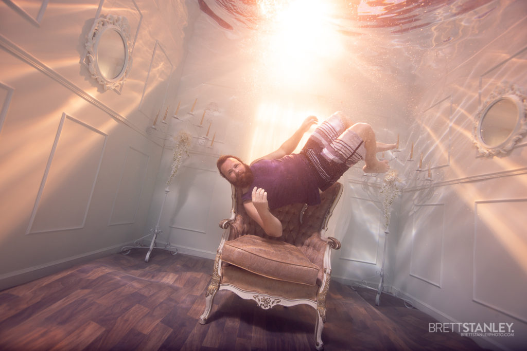 bearded man floating in an underwater room with sunset